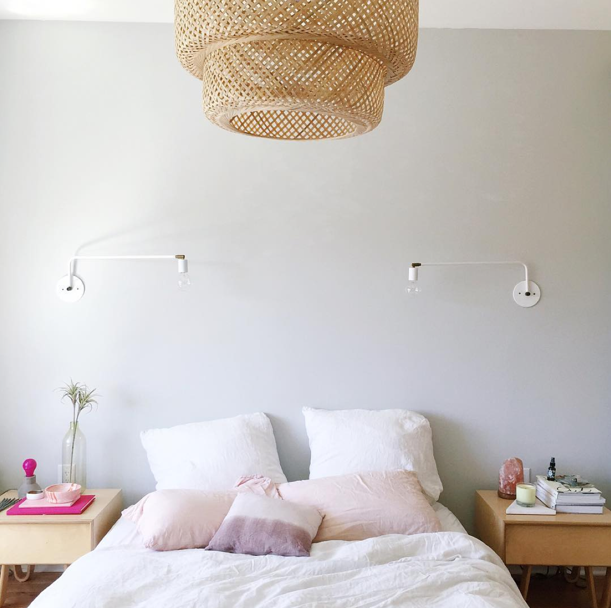 The bedroom of Bri Emery of Design Love Fest. Plain wall with sconces and pale pops of pink. Wicker hanging pendant.
