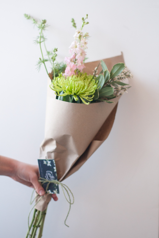 Cut Flowers Wrapped in Kraft Waxed Tissue Paper and Tied with Olive Green Twine with a Business Card Tucked In | Gather Goods